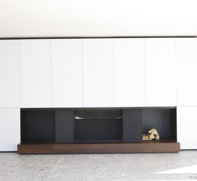 Haardwand met houthaard M-Design Luna, met kasten op maat in wit laminaat gecombineerd met zwarte accenten en hout, voor een strak design.